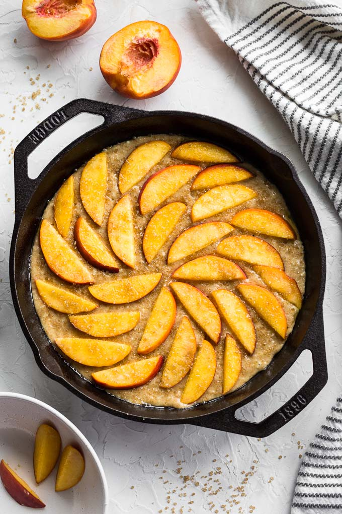 Peach ricotta cake batter in a skillet with peaches arranged on top.