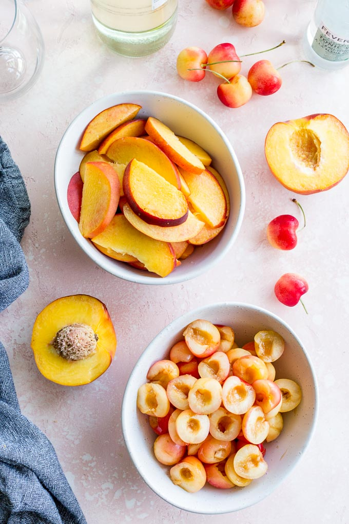 Overhead view of a bowl of cherries and bowl of peach slices.