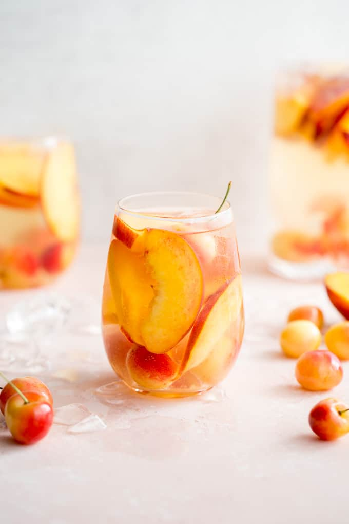 Front view of a stone fruit white wine spritzer in a wine glass with cherries around it.