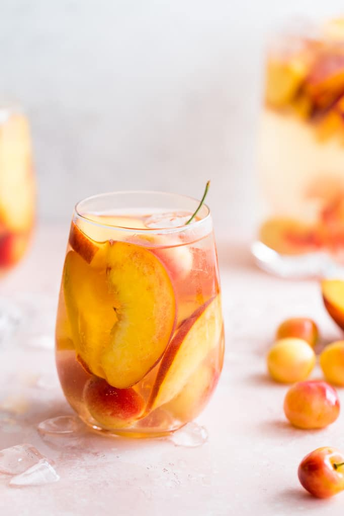 Up-close side view of a stone fruit white wine spritzer in a wine glass.