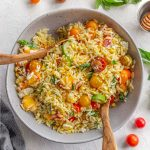 Overhead view of summer orzo salad in a grey bowl with wooden serving spoons inserted into it.