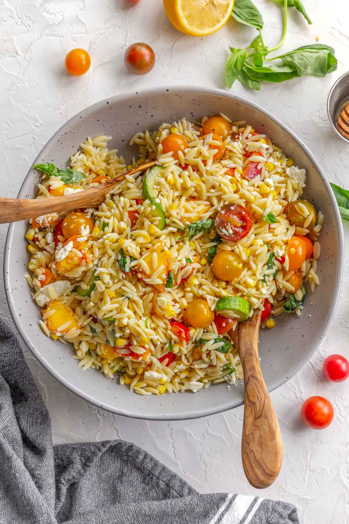 Summer orzo salad in a large grey bowl with two large wooden spoons inserted into it.