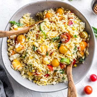 Overhead view of summer vegetable orzo salad in a grey bowl on a white surface.