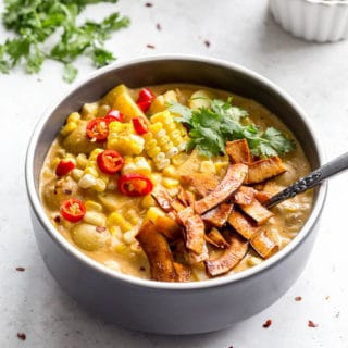 Dairy-free corn chowder in a dark bowl on a light surface with cilantro and coconut bacon in the background.