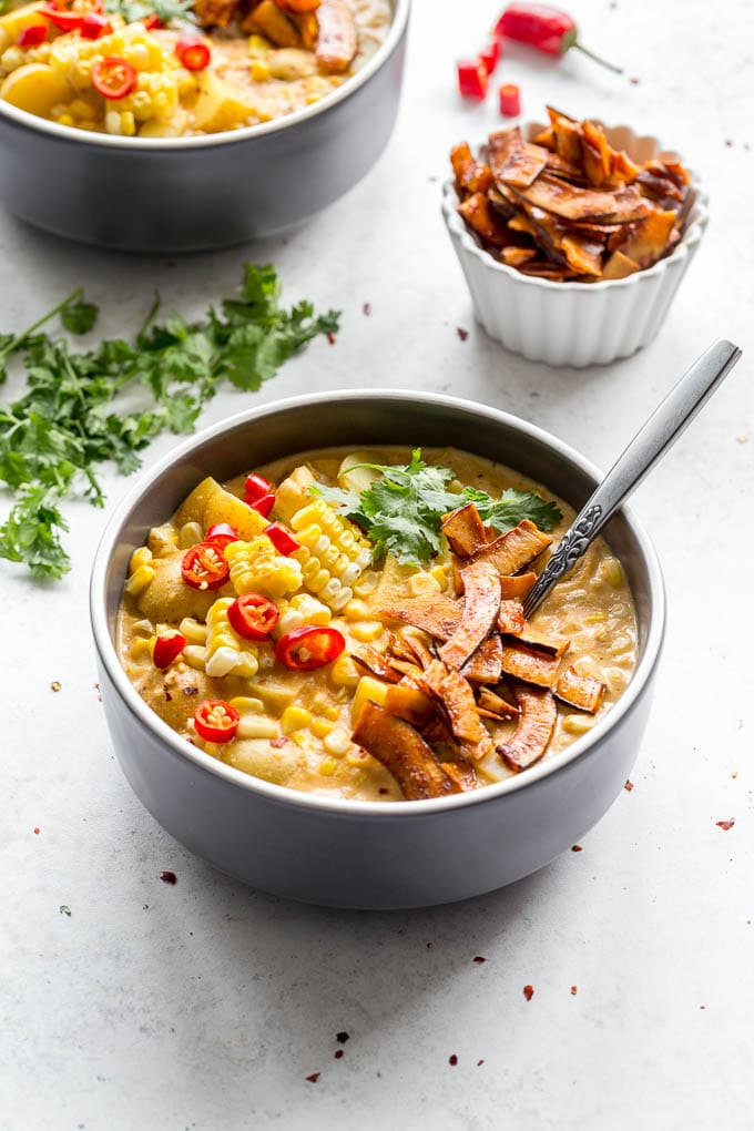 Dairy-free corn chowder with coconut bacon in dark bowls on a light surface.
