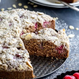 Side view of a slice of lemon raspberry almond crumb cake on a round pan.
