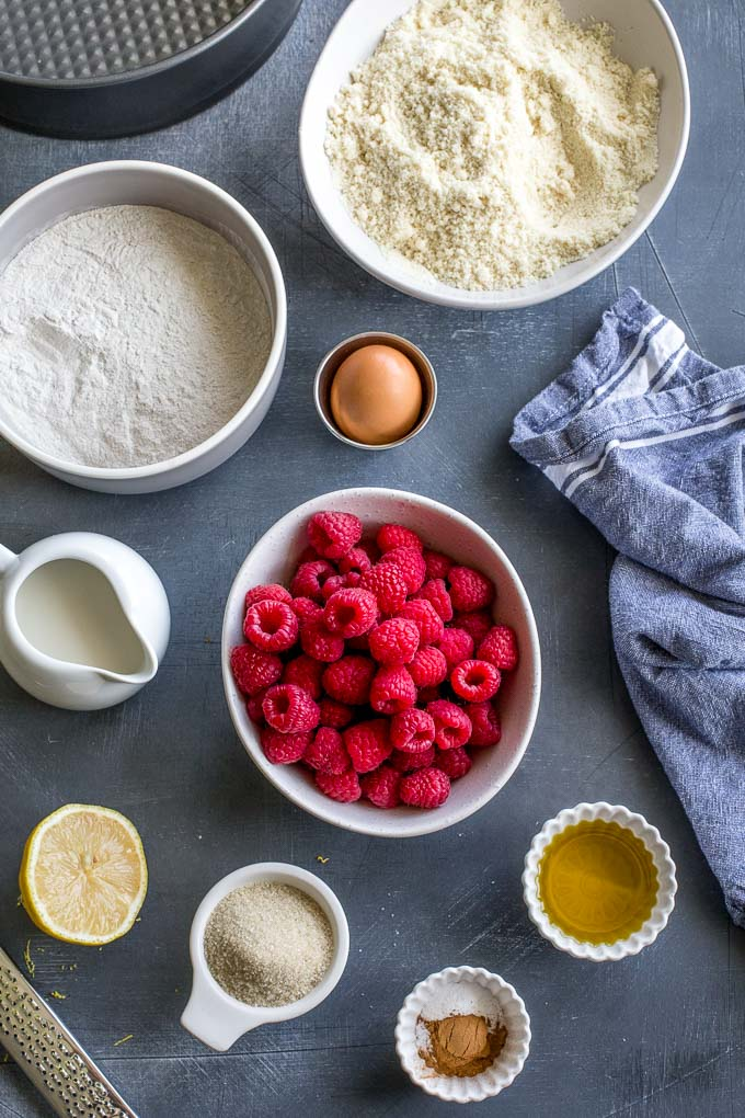 Ingredients to make lemon raspberry almond crumb cake arranged on a dark surface.