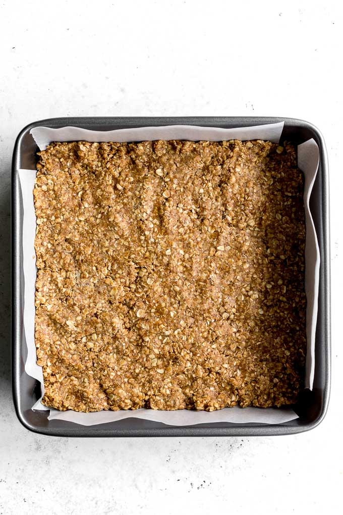 Overhead view of crisp mixture pressed into the bottom of a square pan.