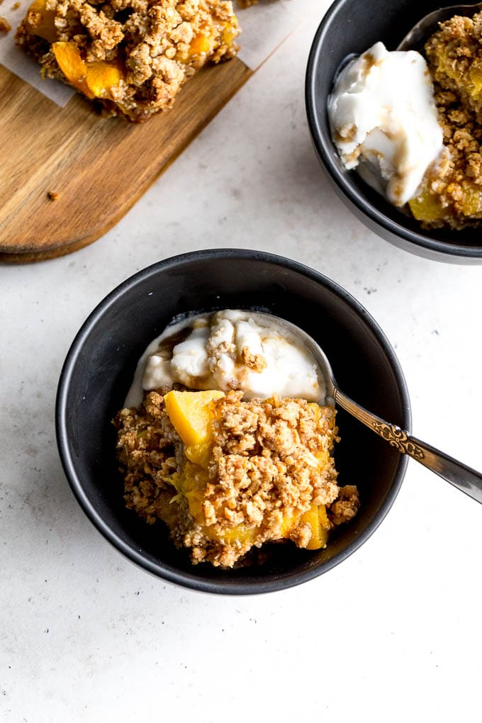 Overhead view of healthy peach crisp bars in black bowls with ice cream.