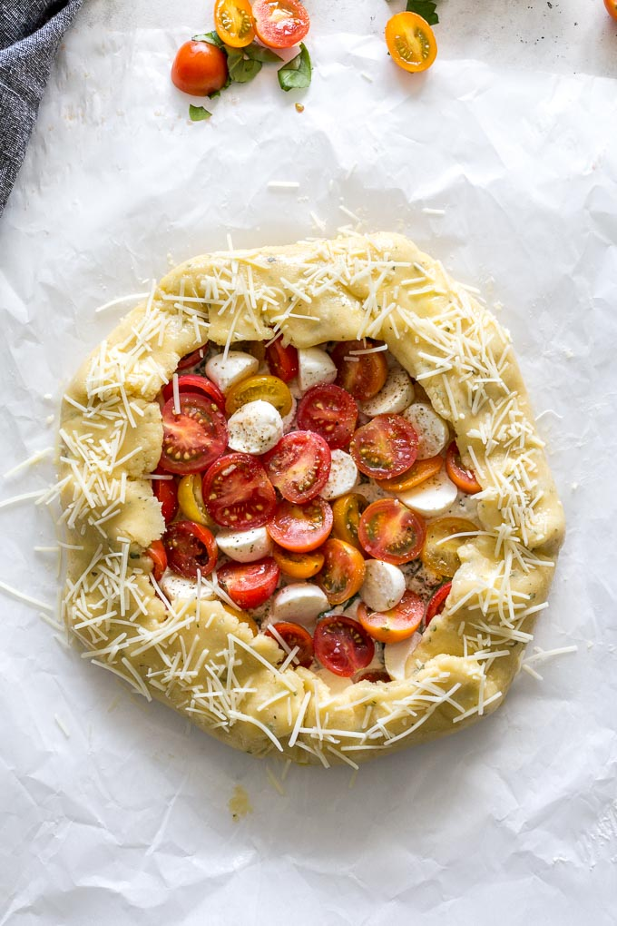 Overhead view of an unbaked tomato galette on a sheet of parchment paper.