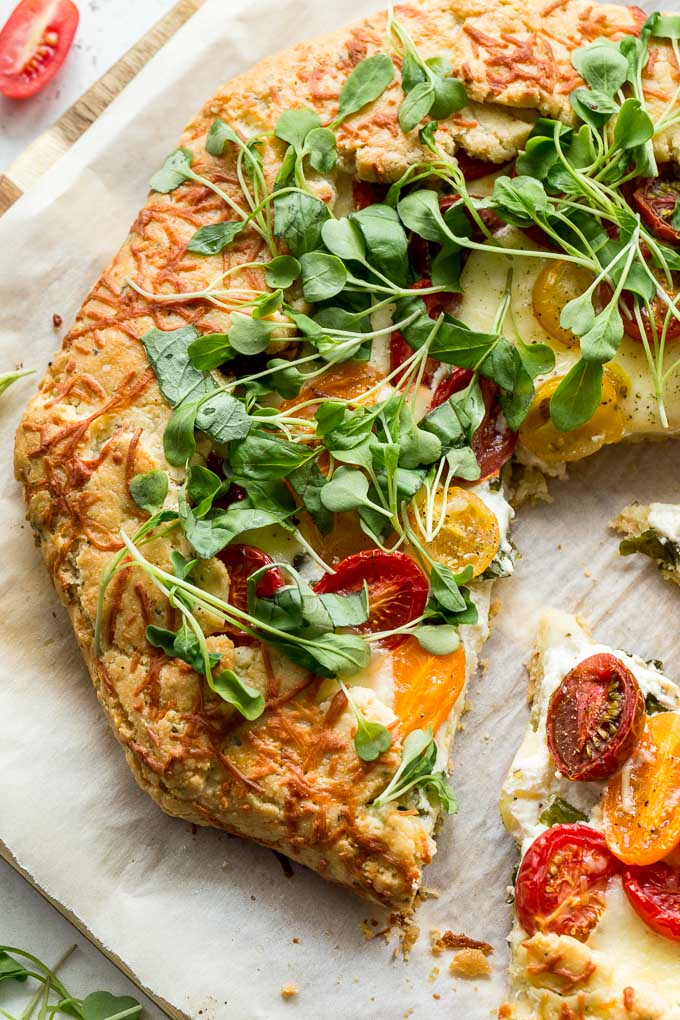 Up-close view of three cheese tomato galette garnished with greens.
