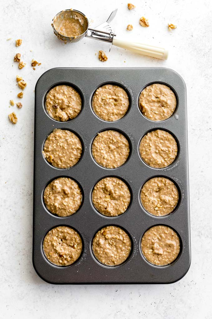 Banana nut muffin batter in a muffin pan on a light coloured surface.