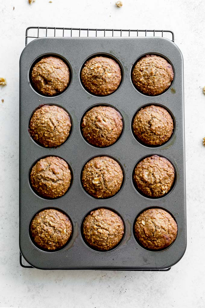 Banana nut muffins baked up in a muffin pan and cooling on a wire rack.