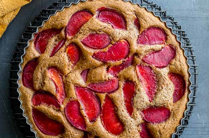 Overhead view of a buttermilk plum cake cooling on a round wire rack on a dark surface.
