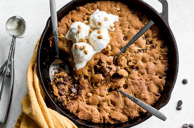 Pecan Chocolate Chip Skillet Cookie with spoons dug into it and ice cream on top.