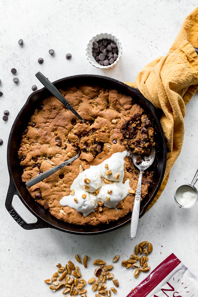 Overhead view of a pecan skillet cookie in a cast iron pan on a light surface with ice cream on top.