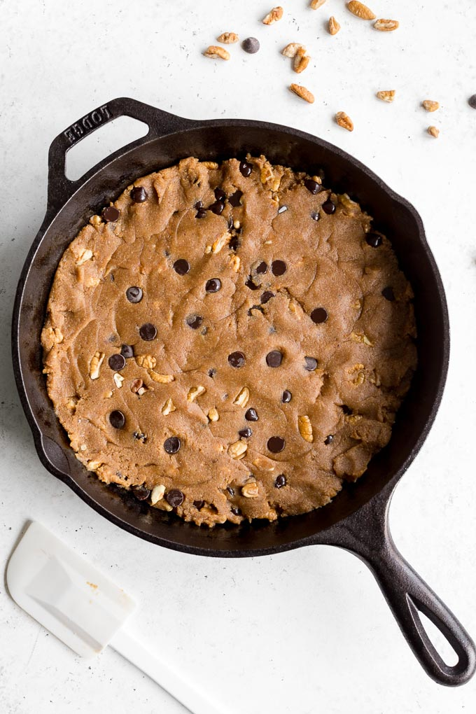 Overhead view of pecan chocolate chip skillet cookie batter spread out into a cast iron skillet.