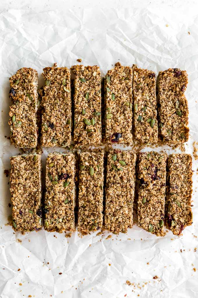 Pumpkin spice granola bars cut into 12 pieces on a sheet of parchment paper.