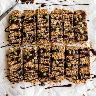 Overhead view of pumpkin spice granola bars on a sheet of parchment paper and topped with melted chocolate and pumpkin seeds.