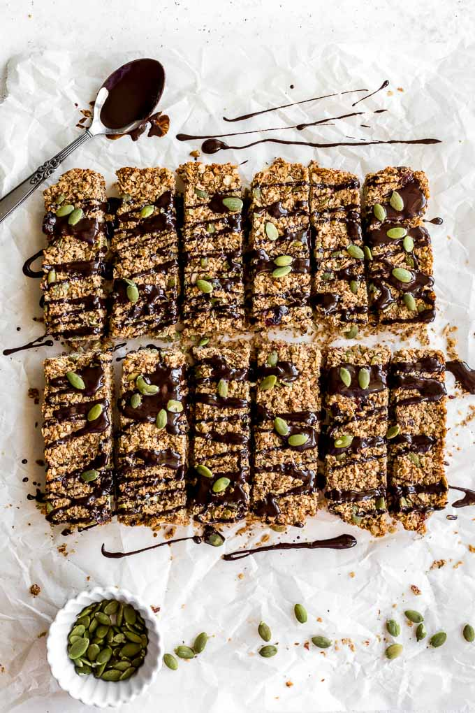 Overhead view of pumpkin spice granola bars on parchment paper with chocolate drizzled over them.