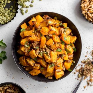 Overhead view of air fryer butternut squash home fries in a black bowl.