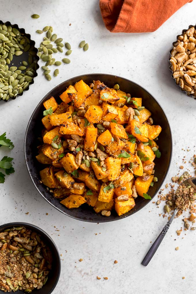 Overhead view of butternut squash home fries in a black bowl.