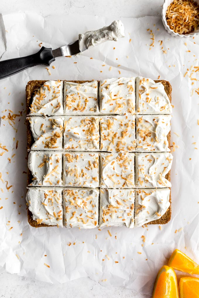 Overhead view of Chai Spice Cake with Orange Cardamom Frosting cut into 16 squares.