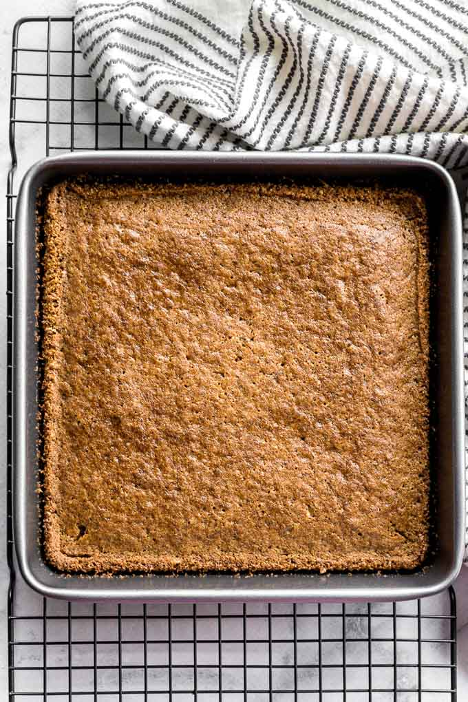 Chai spice cake in a square pan cooling on a wire rack.