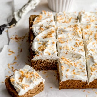 Vegan Chai Cake topped with coconut whip and toasted coconut and cut into squares.