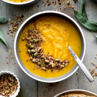 Overhead view of Golden Beet Soup topped with granola and arranged on a grey board.
