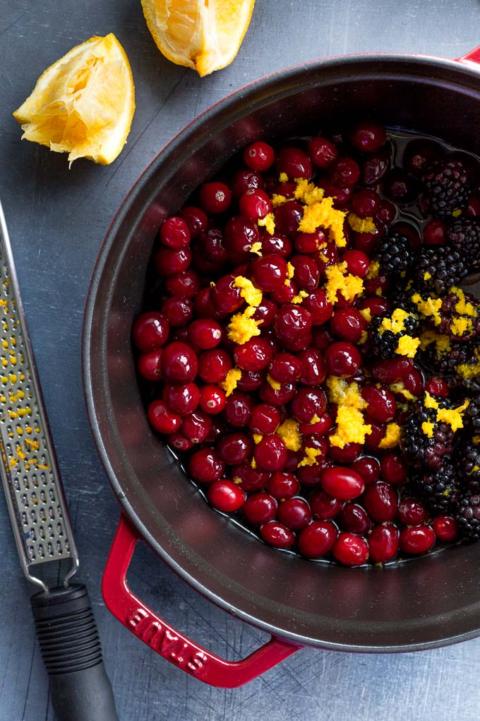 Ingredients to make healthy cranberry sauce in a large pot.