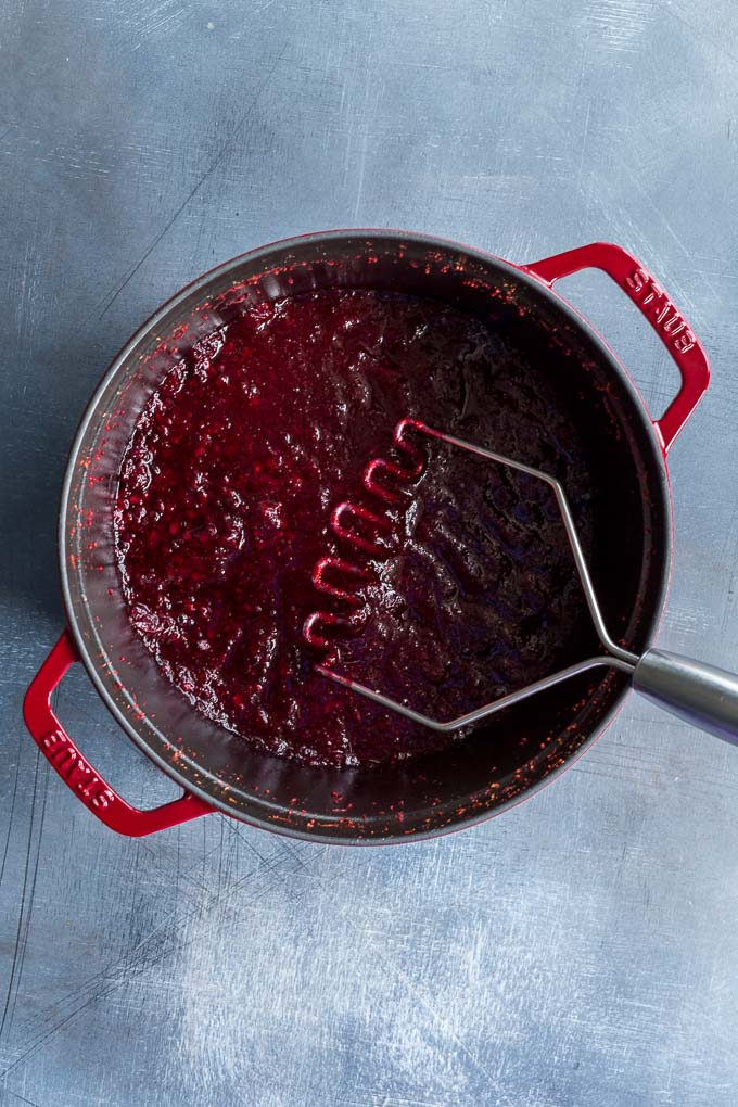 Overhead view of softened fruit for the cranberry sauce being mashed in a large pot.