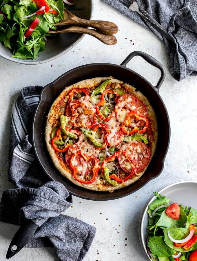 Overhead view of Healthy Homemade Pizza baked up in a cast iron skillet next to a bowl of salad.