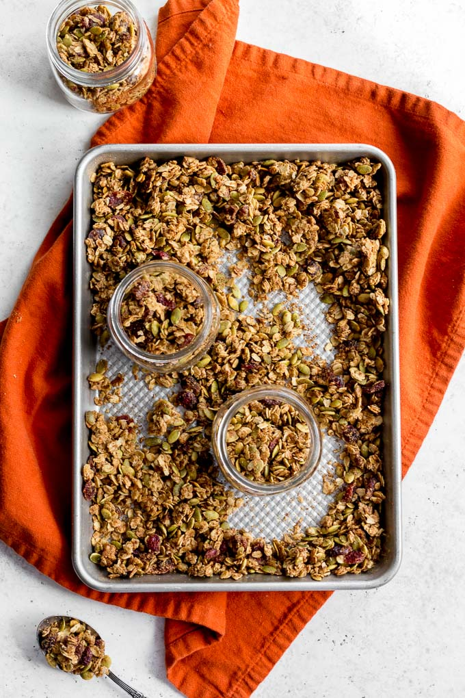 Overhead view of pumpkin spice granola on a baking sheet with small glass jars filled with granola.