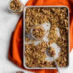 Pumpkin Spice Granola on a baking sheet with granola being spooned into glass jars.