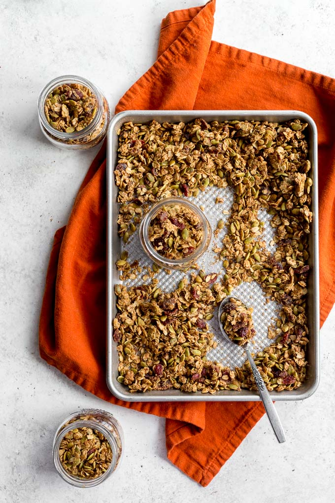 Overhead view of pumpkin spice granola on a baking sheet that's resting on an orange cloth.