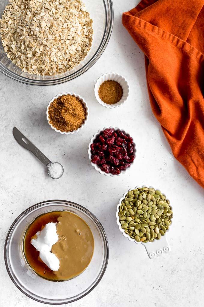 Ingredients to make pumpkin spice granola arranged in individual dishes.