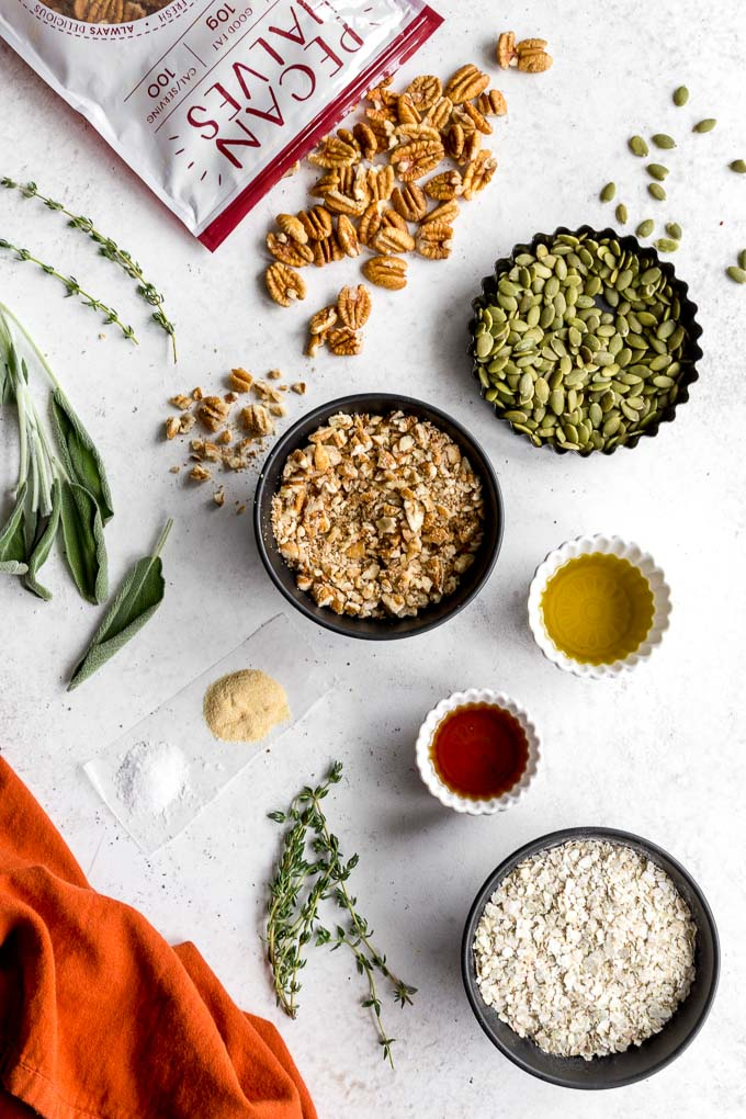 Ingredients to make savoury pecan granola arranged on a light coloured surface.