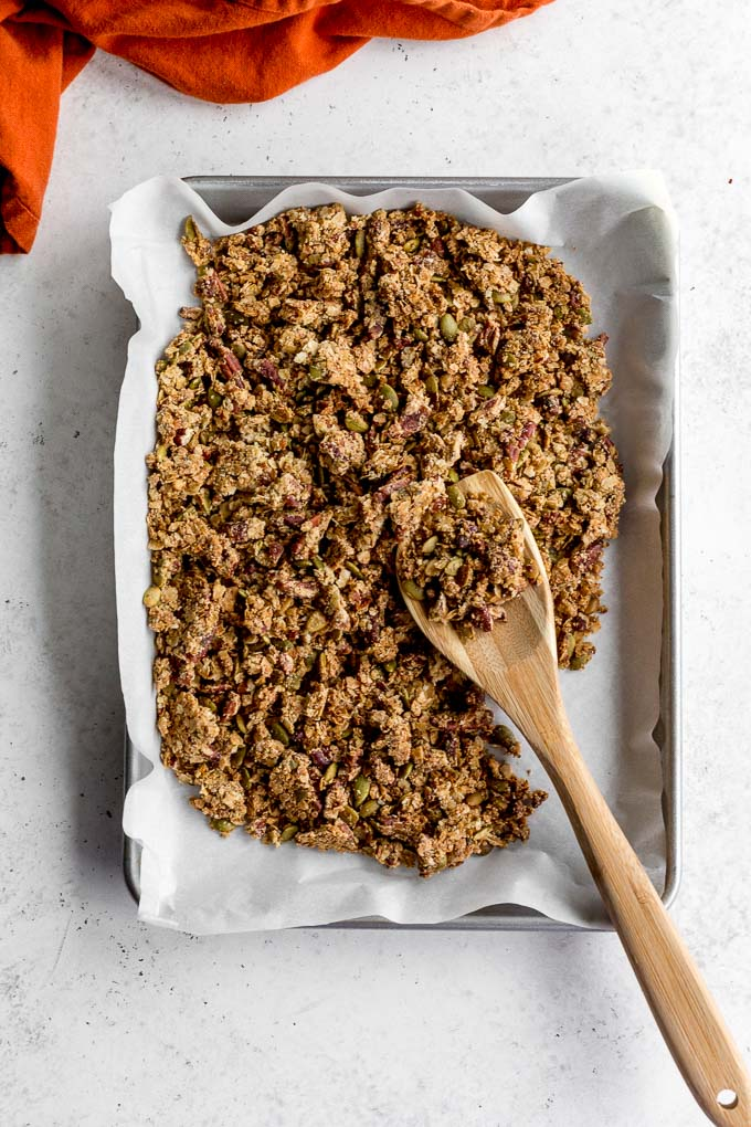 Savoury pecan granola (oven version) on a baking sheet with a wooden spoon.