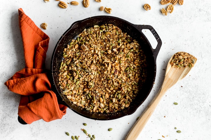Pecan granola in a cast iron skillet with a wooden spoon next to it.