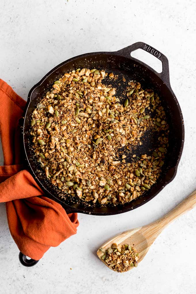 Overhead view of savoury pecan granola in a cast iron skillet with an orange napkin wrapped around the handle.