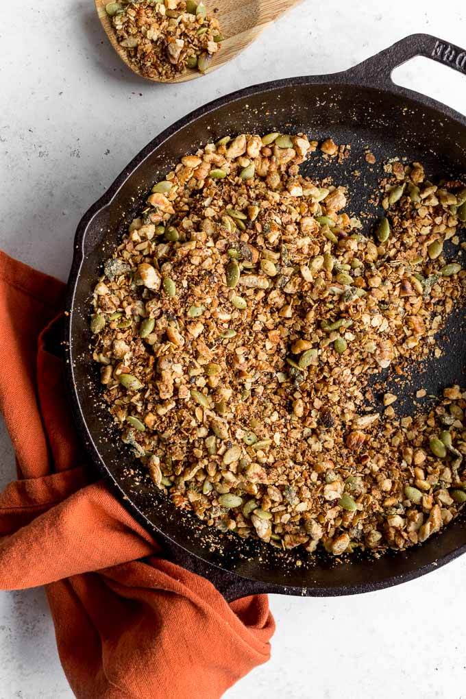 Up-close view of savoury pecan granola in a cast iron skillet.