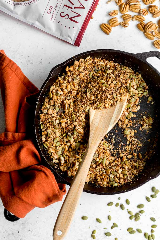 Savoury pecan granola in a skillet with a wooden spoon and pecans off to the side.