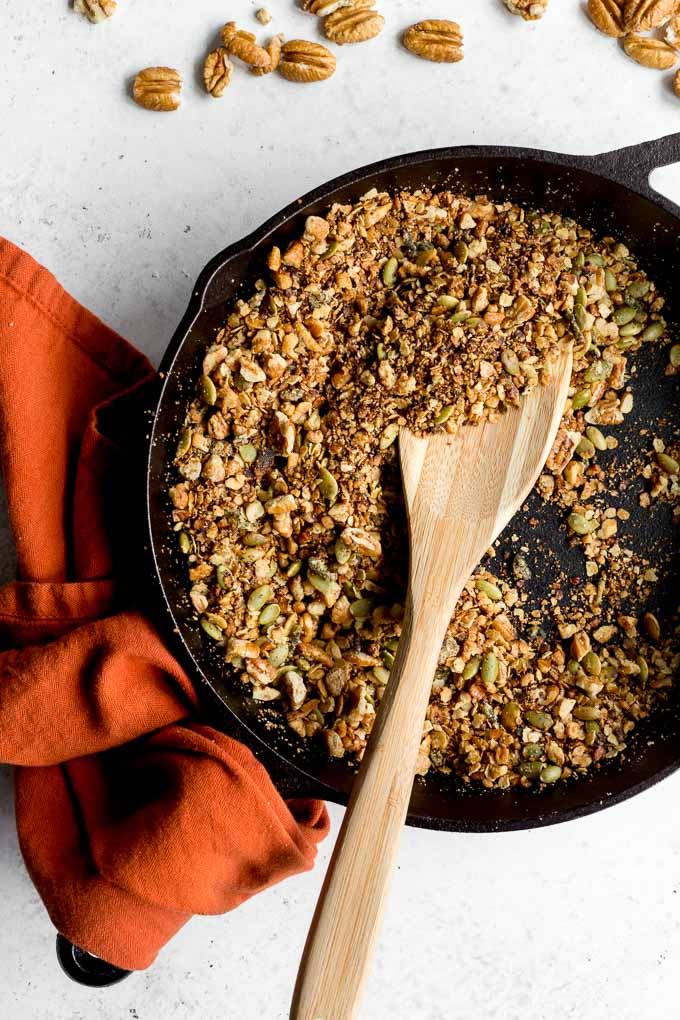 Overhead view of savoury pecan granola in a cast iron skillet with a wooden spoon.
