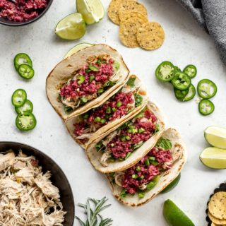 Overhead view of Slow Cooker Chicken Tacos arranged on a white surface and topped with salsa.