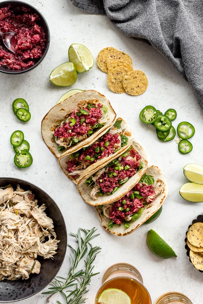 Overhead view of Slow Chicken Chicken Tacos assembled and topped with cranberry salsa.