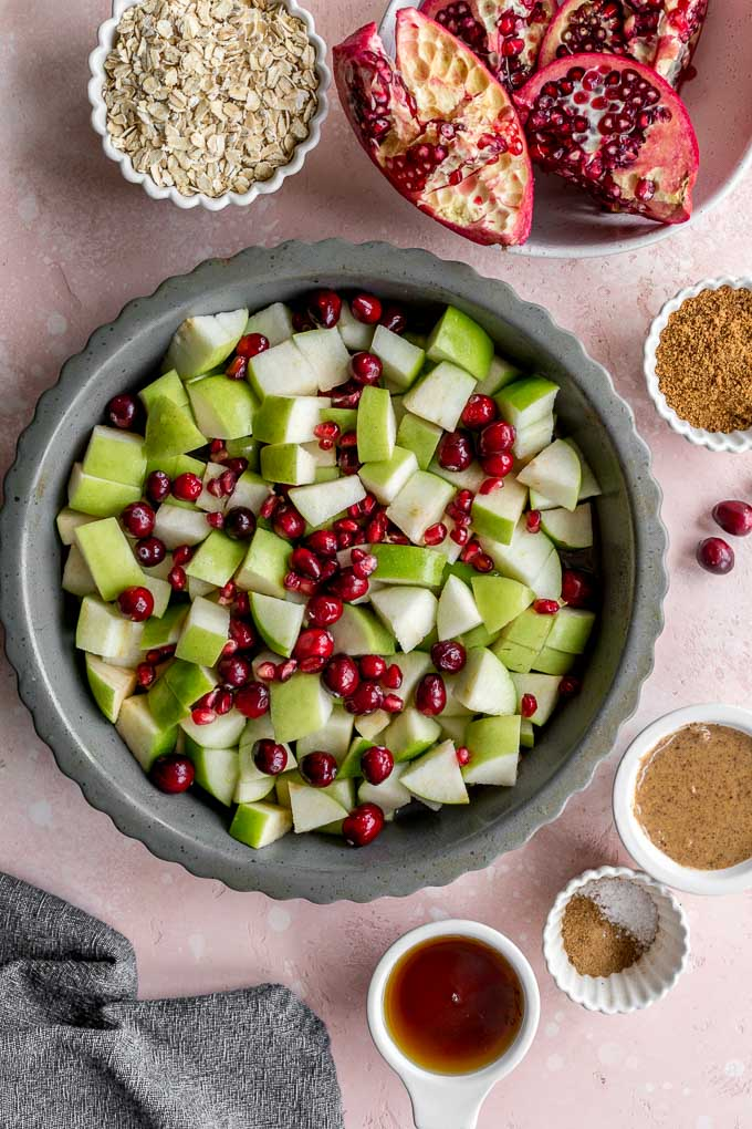 Chopped granny smith apples, cranberries and pomegranate arils mixed together in a grey pie plate.