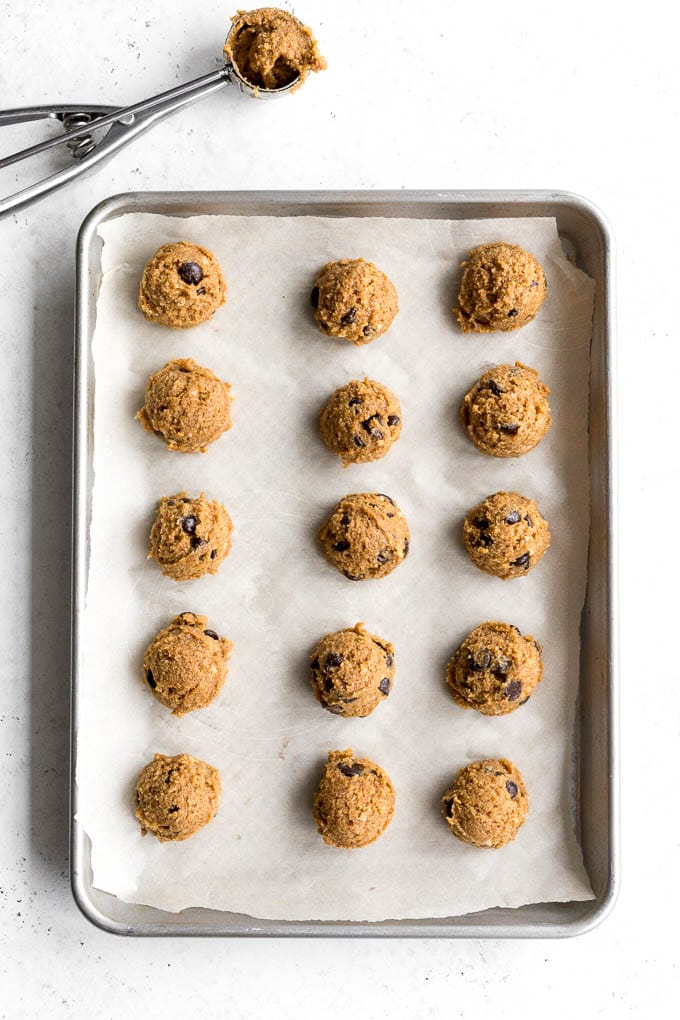 Scoops of cookie dough arranged on a baking sheet.