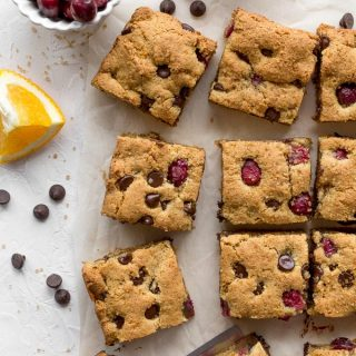 Overhead view of Cranberry Chocolate Chip Cookie Bars cut into squares next to cranberries and chocolate chips.