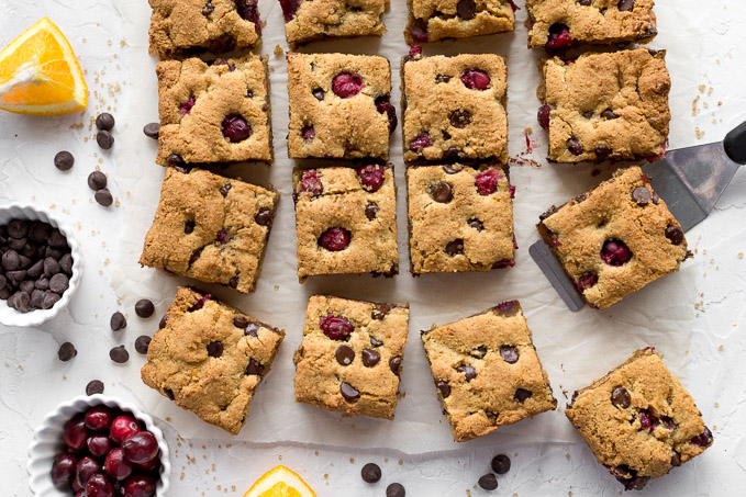 Cranberry cookie bars arranged on a sheet of parchment paper.
